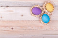 Three colorful eggs in small nests on wooden background top view Stock Image