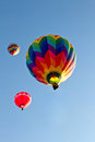Three colorful hot air balloons ascending into sky multi color the blue clear Stock Photo
