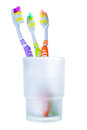 Three colorful toothbrushes in glass isolated on white Stock Images