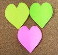 Three colors of heart shaped memo papers with clips on board Royalty Free Stock Images