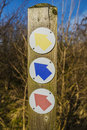 Three coloured arrows giving directions on wood post Stock Images