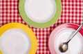 Three coloured plates and a spoon on checkered table cloth Royalty Free Stock Images