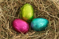 Three colourful easter eggs nestled straw Stock Photography