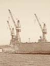 Three cranes in the port of Hamburg in vintage look Royalty Free Stock Photo