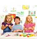 Three creative kids on the lesson years old boy and girls with glue and paints table Royalty Free Stock Photo