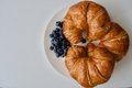 Three croissants and blue blueberries Royalty Free Stock Photo