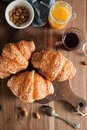 Three croissants with cheese crust lie on a wooden board on a wooden table next to tea, almonds, apricot jam and spoon Royalty Free Stock Photo