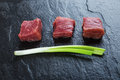 Three cubes of meat and green onions