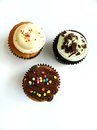 Three cupcakes with candy sprinkles a photograph showing beautifully handmade cream cup cakes colourful candies sprinkled on top Stock Photo