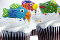 Three cupcakes decorated with candy fish Stock Images