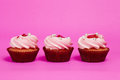 Three cupcakes on the pink background Stock Images