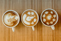 Three cups of cafe' latte with three shapes of latte art Royalty Free Stock Photo