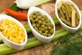 Three cups of corn green peas and beans pepper leek Royalty Free Stock Images