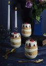 Three Cups Of Raspberry Cream Parfait On A Blue Table With Candles