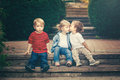 Three cute funny adorable white Caucasian children toddlers boys girl sitting together kissing each other Royalty Free Stock Photo