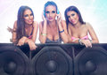 Three cute girls listening music on large speaker Royalty Free Stock Images