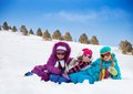 Three cute girls looking kids laying in snow together on sunny day Royalty Free Stock Photo