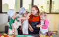 Three cute kids are preparing a fruit salad in kitchen Royalty Free Stock Photo