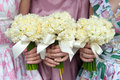 Three daffodil wedding bouquets held by bridesmaids in vintage dresses Stock Photos