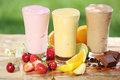 Three delicious smoothies with yoghurt or ice cream blend two made fruit and one of chocolate together various fresh Royalty Free Stock Photos