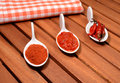 Three different forms of red hot chili canned sauce and powder in white porcelain spoons Royalty Free Stock Photography