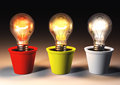Three different light bulbs lit with color are growing in colored pots that lie on a dark background Stock Images