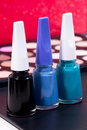 Three different nail polish colors and a make up background - black, blue, green Royalty Free Stock Photo