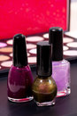 Three different nail polish colors and a make up background - pink, dark pink and shimmery green Royalty Free Stock Photo