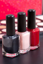 Three different nail polish colors and a make up background - red, neutral and black Royalty Free Stock Photo