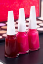 Three different nail polish colors and a make up background - red, pink and light pink Royalty Free Stock Photo