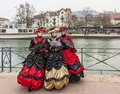 Three disguised persons annecy france march a group of poses near a water canal during the annecy venetian carnival yearly in Royalty Free Stock Photos