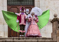Three disguised persons annecy france march show a beautiful scene in front of a wooden gate during the annecy venetian carnival Stock Photos