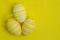 Three easter eggs against yellow background Royalty Free Stock Image