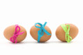 Three easter eggs with pink blue and green ribbon on white Stock Images