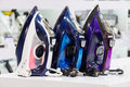 Three electric irons in retail store colored at shelf defocused background Royalty Free Stock Image