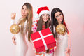 Three elegant young women on new new year s eve beautiful caucasian holding gift box and christmas decoration christmas and Royalty Free Stock Images