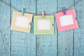 Three empty photo frames hanging with clothespins colorful or notes paper on wooden blue vintage shabby chic background Stock Photos