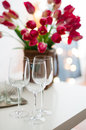Three empty wine glasses on a table and bouquet of flowers in daylight Stock Image