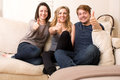 Three enthusiastic teenagers giving a thumbs up two attractive young girls and boy sitting close together on sofa gesture of Royalty Free Stock Photos