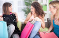 Three excited young girls after shopping at home beautiful women with bags relaxing on sofa Royalty Free Stock Photo