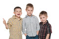 Three fashion young boys on the white are standing together background Royalty Free Stock Photo