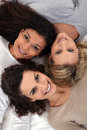 Three female friends laying together Stock Image