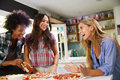 Three Female Friends Making Pizza In Kitchen Together Royalty Free Stock Photo