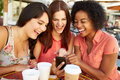 Three Female Friends Reading Text Message In CafŽ Royalty Free Stock Photo