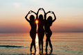 Three female silhouettes hands making a heart shape with sunset