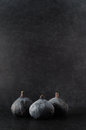 Three figs grouped on black in a still life composition slate surface with dusty background shot just above eye level Royalty Free Stock Photos