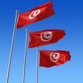 Three flags of Tunisia against blue sky. Stock Photography