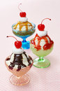 Three flavors of ice cream sundaes in vintage glass dishes chocolate berry and caramel each sundae is topped with whipped and a Royalty Free Stock Photography