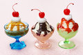 Three flavors of ice cream sundaes in vintage glass dishes chocolate berry and caramel each sundae is topped with whipped and a Stock Image