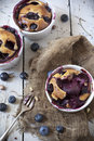 Three french clafoutis with blueberries and cherries on ceramic ramekins on rustic white vintage background canvas fork Royalty Free Stock Photos